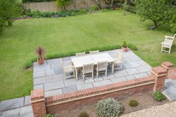 Large UK back garden with lawn and wooden patio furniture on a terrace in summer