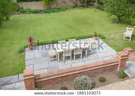 Large UK back garden with lawn and wooden patio furniture on a terrace in summer Stock photo ©