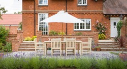 Large UK country house with garden furniture on a patio in a back garden