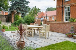 Large UK property, house with back garden, wooden furniture table and chairs on patio terrace