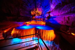 Large underground waterfall in cave on tour path with orange and blue lights