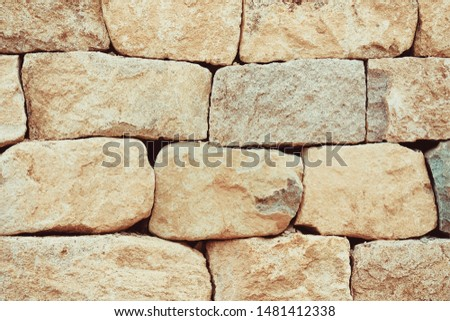 Large unpaved cobblestones, old wall, fortress. Beige tones. #1481412338