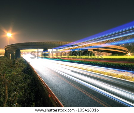 Large urban ring highway viaduct long exposure photo light trails night scene