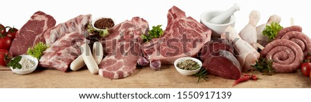 Large variety of fresh raw meat for a barbecue with beef steak, sausage, chicken, pork, spare ribs and nackensteak displayed with herbs in a panorama banner suitable for butchery advertising