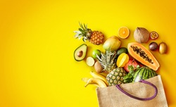 Large variety of healthy fresh tropical fruit on exotic yellow background with copy space and vignette in panorama banner format
