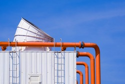 Large ventilation chimney with orange pipelines and exhausting machine system on factory building roof against blue sky background