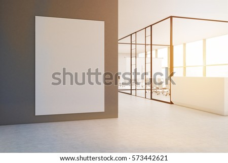 Large vertical poster is hanging on a gray wall in an office with glass walls and a white reception desk. 3d rendering. Mock up. Toned image #573442621
