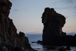 Large volcanic rock formation known as Kerling or the Troll Woman with a face shape on the side of it, at Djupalonssandur beach at sunset on the Snaefellsnes Peninsula of Iceland