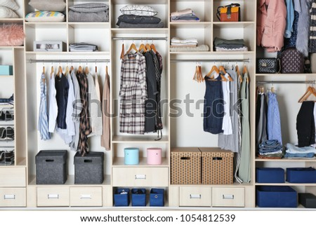 Large wardrobe closet with different clothes and home stuff