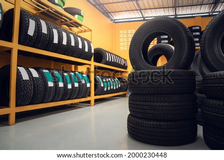 Large warehouse of car tires, rack with customer car tires in warehouse of a tire dealer