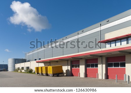 large warehouse with red loading docks and several trailers for rent