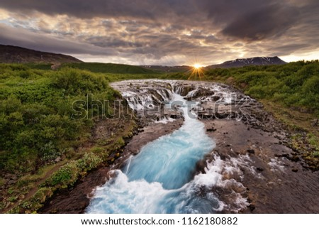 Large waterfall in a wide landscape with evening light, sunset with rays on a mountain range, water movement in long exposure - Location: Iceland, Golden circle, Bruarfoss