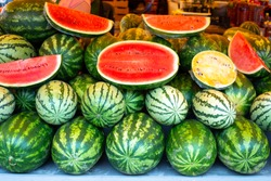large watermelons of red and yellow colors lie on the table, in a cut, for sale in the eastern market