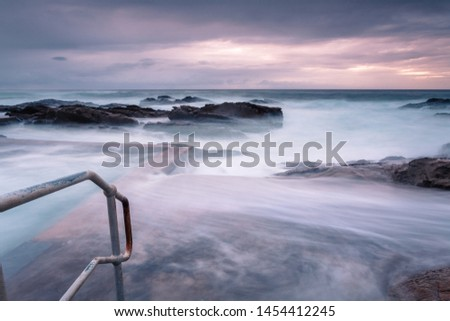 Large waves and swell engulf the public rock pool.  Long exposure  creates a mystical feel of what was a tempestuous ocean Foto stock ©