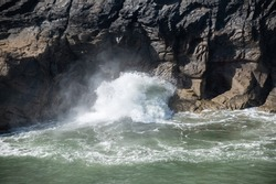 Large waves blowing through a hole in rocks in Boscastle