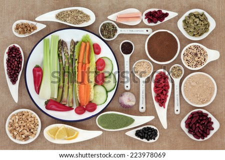 Large weight loss diet health food selection in porcelain bowls and measuring spoons over brown paper background.