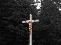 Large white and gold crucifix in a small cemetery on a hill - isolated colour with dark trees in the background