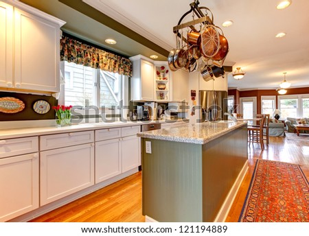 Large white and green kitchen with hardwood floor.