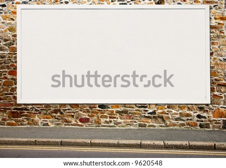Large white blank billboard on a colorful stone wall.