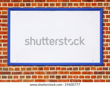 Large white blank billboard sign with a blue wooden frame on a red brick wall.
