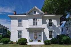 Large white clapboard house with portico entrance and gable