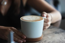 Large white Cup with cappuccino in female hands, selective focus