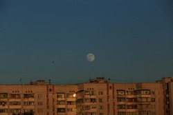 large white full moon on clear blue over an urban high building in evening summertime