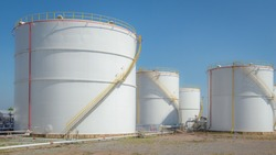 large white Industrial tanks for petrol and oil with blue sky.Fuel tanks at the tank farm. metal stairs on the side of an industrial oil container.Staircase on big fuel tank