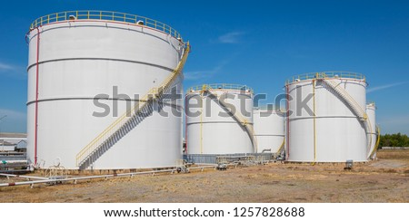 large white Industrial tanks for petrol and oil with blue sky.Fuel tanks at the tank farm. metal stairs on the side of an industrial oil container.Staircase on big fuel tank stock photo