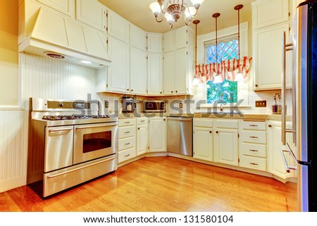 Large white kitchen in an old AMerican house with hardwood floor. - stock photo