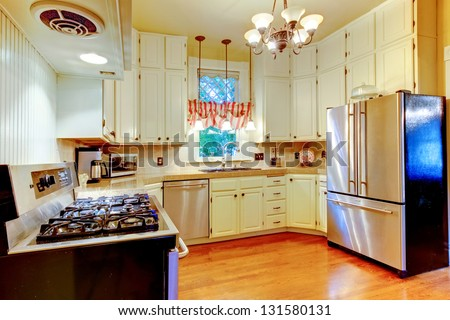 Large white kitchen in an old AMerican house with hardwood floor.