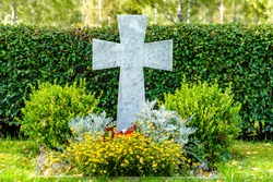 Large white marble cross on a beautiful and well cared but unmarked grave on a cemetery in Sweden in beautiful autumn sunlight