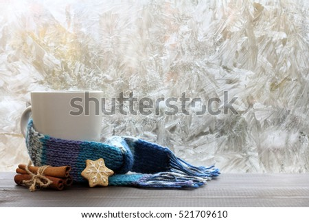 large white mug with blue scarf standing on a table with cinnamon and ginger cookies / warming drink on a winter day #521709610