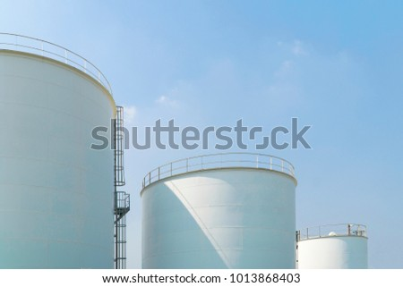 Large white water tank with blue sky.