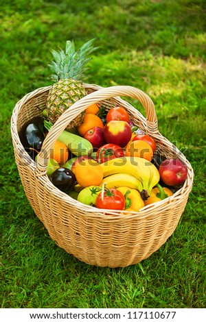 Large wicker basket with fruits and vegetables is on green grass.