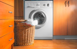 Large Wicker Laundry Basket, Lid Opened, Near the Front Load Washing Machine with Laundry. House Interior Laundry Room. Wood Interior Design.
