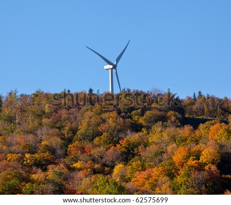 Large wind generator on hilltop above autumn trees