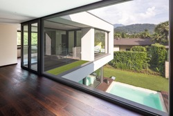 Large window in hallway of modern villa overlooking the private pool. Nobody inside