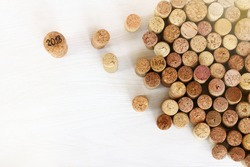 large wine cork with the number 2018 next to a lot of older ones on the table top view / different from others