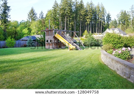 Large wood play ground for kids at private home spring back ground.