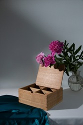 Large wooden box with a separator on a light mint background empty. Product Display Concept. Large pink peonies in a transparent vase. Copy space. Oak box on the table, for installation