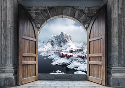 Large wooden door open with fishing village and rocky mountains on coastline in winter at Hamnoy, Lofoten Islands, Norway