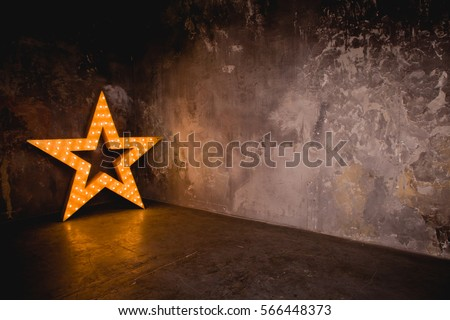 Large wooden star with a large number of lights are lit. Beautiful decor, design. Loft style Studio. Dark concrete background. Christmas, holiday, honorary star. Five stars 5 stars #566448373