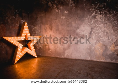 Large wooden star with a large number of lights are lit. Beautiful decor, design. Loft style Studio. Dark concrete background. Christmas, holiday, honorary star. Five stars 5 stars #566448382