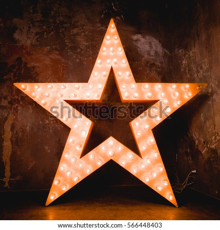 Large wooden star with a large number of lights are lit. Beautiful decor, design. Loft style Studio. Dark concrete background. Christmas, holiday, honorary star. Five stars 5 stars #566448403