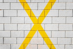 Large X shaped yellow cross painted on the pavement, background of a parking lot.