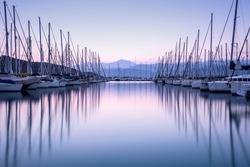 Large yacht harbor in purple sunset light, luxury summer cruise, sailboats in sunrise, leisure time, active life, vacation and holidays concept