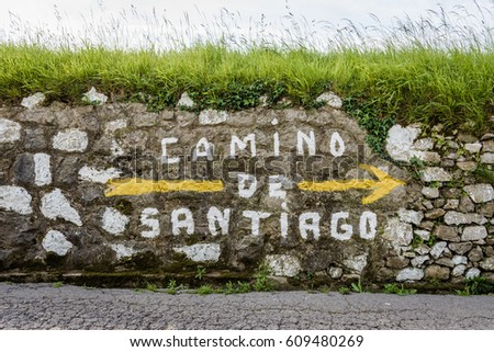 Shutterstock Large yellow arrow and inscription Camino de Santiago on wall along the way of the Way of St. James in Spain