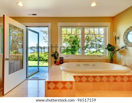 Large yellow bathroom with tub and lake view and open door.