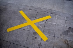 Large yellow colored X sign painted on the pavement